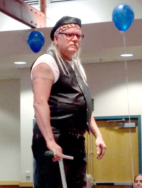 Cliff Kauffman, director of retail for Goodwill of the Southern Alleghenies, dons biker gear for a fashion show Wednesday during Goodwill's Report to the Community gathering at Pitt-Johnstown's Living Learning Center.