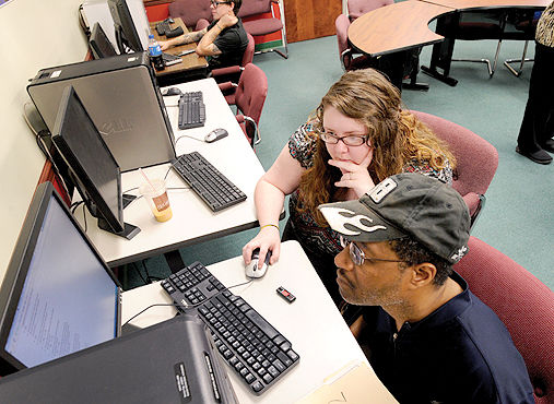 Goodwill Job Center Jen Pfeil, an employment counselor at the Goodwill Career Center, helps Anthony Wiley of Johns­town search for work at a computer station.