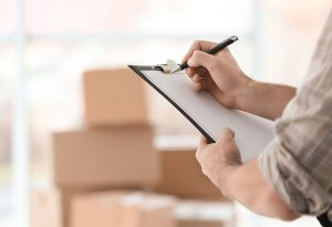 Senior Move Manager holding clipboard with list of items