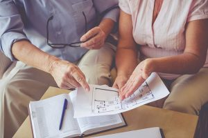 Senior couple sitting on couch looking at floor plan